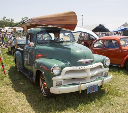 chevy: IOLA, WI - JULY 13:  1954 Chevy 3100 Pickup truck with Wooden Canoe on Top at Iola 41st Annual Car Show July 13, 2013 in Iola, Wisconsin.