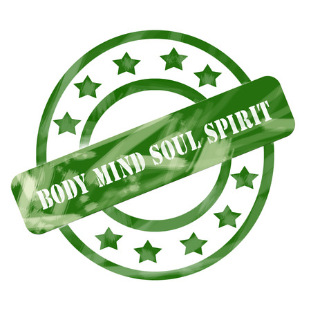 A green ink weathered roughed up circles and stars stamp design with the words Body Mind Soul Spirit on it making a great concept. Stock Photo