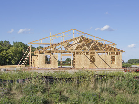 rafters: A large building framed during construction with rafters under a blue sky.