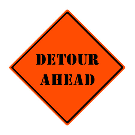 An orange and black diamond shaped road sign with the words DETOUR AHEAD making a great concept. photo