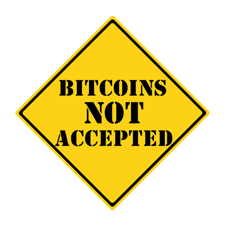 A yellow and black diamond shaped road sign with the words BITCOINS NOT ACCEPTED making a great concept. Stock Photo