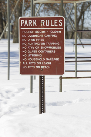 rule: A brown Park Rules sign in the snow at a public park.