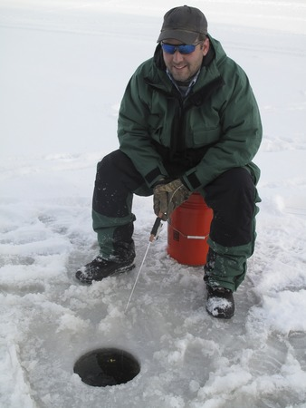 Happy Man sitting on an orange five gallon bucket Ice Fishing with pole in hand over bobber in hole in ice. photo