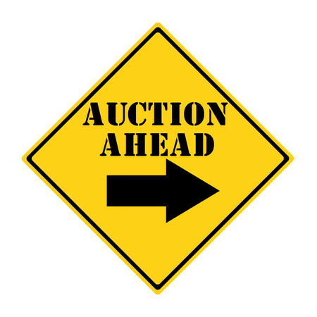 A yellow and black diamond shaped road sign with the words AUCTION AHEAD making a great concept. Imagens
