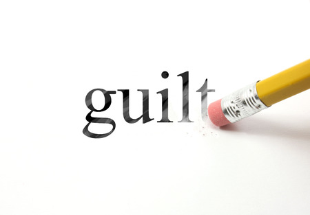 The word Guilt written with a pencil on white paper.  An eraser from a pencil is starting to erase the word guilt.