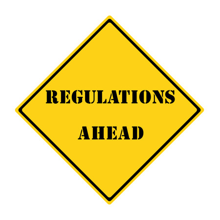 A yellow and black diamond shaped road sign with the word REGULATIONS AHEAD making a great concept. Stock Photo