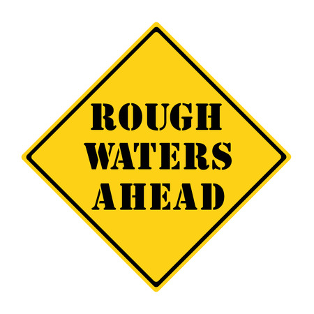 rough road: A yellow and black diamond shaped road sign with the words ROUGH WATERS AHEAD making a great concept.