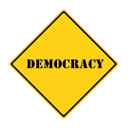 A yellow and black diamond shaped road sign with the words DEMOCRACY making a great concept.