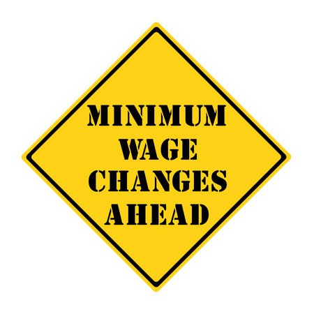 A yellow and black diamond shaped road sign with the words MINIMUM WAGE CHANGES AHEAD making a great concept.