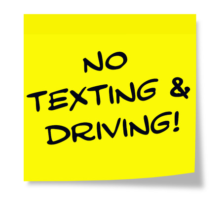 No Texting and Driving written on a paper yellow Sticky Note making a great concept. photo