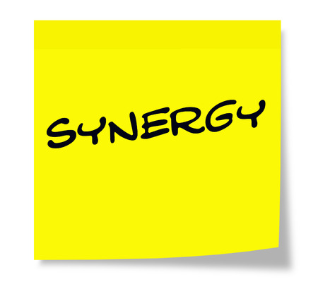 sinergia: Synergy written on a yellow sticky note making a great concept. Foto de archivo