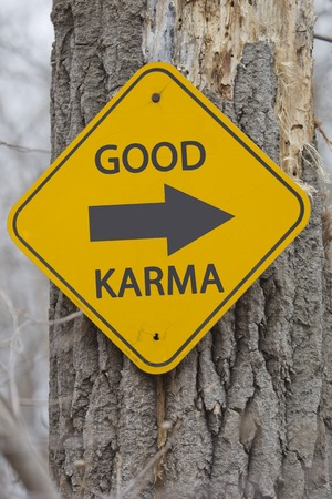karma: Good Karma with an arrow on a yellow sign on a tree making a great concept.