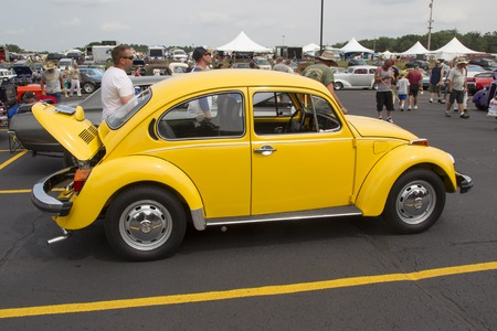 vw: IOLA, WI - JULY 11:  Side of 1976 VW Yellow Bug  Beetle Car at Iola 43nd Annual Car Show July 11, 2015 in Iola, Wisconsin.
