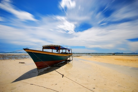 Fisherman boat on low tide shore photo