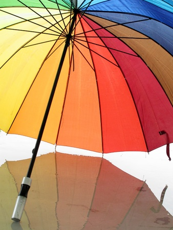 Opened multicolored umbrella with reflection                           Stock Photo - 13269455