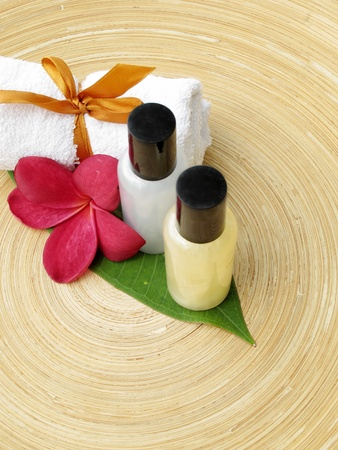 Spa Concept  bottles of lotion, towel   flower on wooden plate  photo