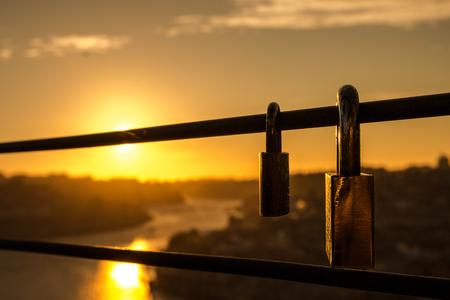 Two padlocks stuck on the bridge at sunset