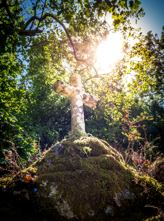 Sun illuminating a Franciscan stone cross Stock Photo