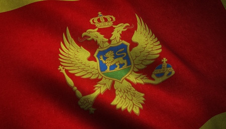 Realistic flag of Montenegro waving with highly detailed fabric texture. Stock Photo