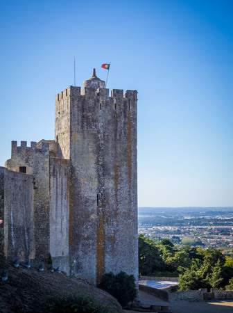 Palmela, Portugal - October 22. Portugal flag raised on top of the main tower of the castle of Palmela in Portugal during a sunny day. Stock Photo