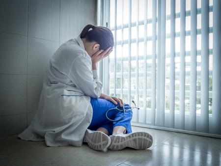 Tired doctor sitting alone in hospital floor near window