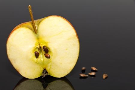 pips: de helft van de appel met een aantal pips op donkere achtergrond Stockfoto