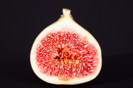 sectioned: single sectioned fresh fig on black background Stock Photo