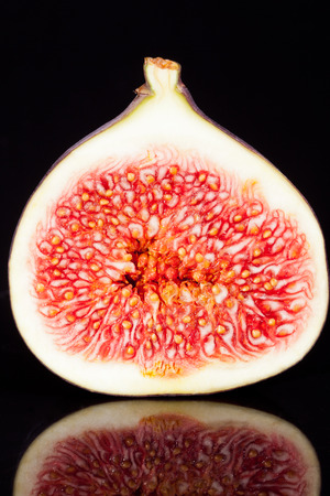 sectioned: half of  sectioned fresh fig on black background-macro