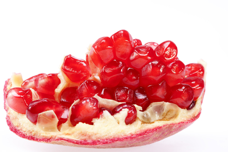 a pomegranate: piece of fruit of red pomegranate isolated on white background, close up. Stock Photo