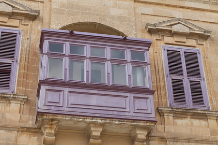 Typical wooden balcony with shutter on old building in Mdina, Malta, Europe Stock Photo