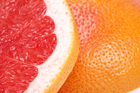 sectioned: half of red fruit of grapefruit , close up.