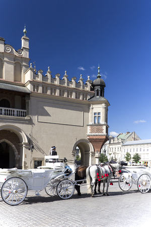 main market: CRACOW, POLAND, July 22, 2013 :  Old-styled horse carriage on main market square next to Cloth Hall. Cracow is the most visited city in Poland by tourists. Editorial