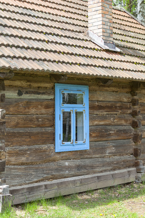 ethnographic: old traditional wooden polish cottage with blue window in open-air museum, Ethnographic Park, Kolbuszowa, Poland Editorial