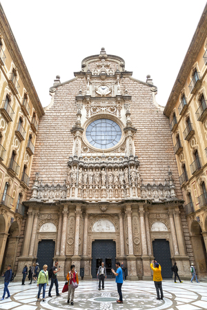 virgin of montserrat: MONTSERRAT, SPAIN - MAY 10, 2016 :Tourists on the courtyard in front of Santa Maria de Montserrat Abbey, Catalonia. It  is a Benedictine abbey located on the mountain of Montserrat,  known for the cult statue of Virgin Mary.