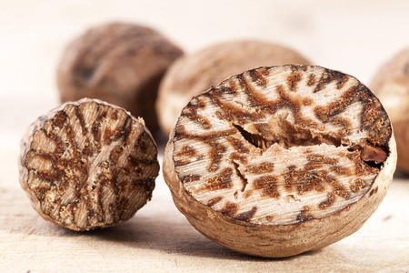 Nutmeg , whole and half on wooden plank, close up Stockfoto