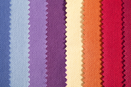 Background of colorful vertical stripes of serrated cotton fabric, close up
