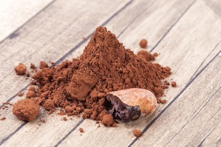 Cocoa beans and powder on wooden plank. Stock Photo