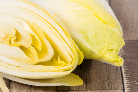 escarola: Vegetables of Belgian endive on wooden plank, close up