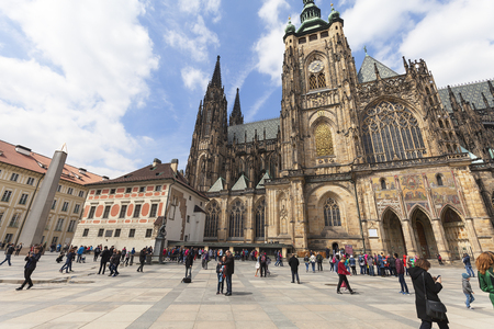 PRAGUE, CZECH REPUBLIC - MAY 1 :  14th century St. Vitus Cathedral and Castle courtyard with tourists in sunny day. It  is a Roman Catholic metropolitan cathedral in Prague, the seat of the Archbishop of Prague. Editorial