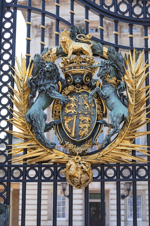 Buckingham Palace, decorative entrance gate with Royal coat of arms, London, United Kingdom. Palace is the London residence and administrative headquarters of the reigning monarch of the United Kingdom