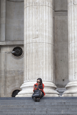 st: LONDON, UNITED KINGDOM - JUNE 22, 2017: 18th century St Paul Cathedral, majestic columns and woman sitting on the stairs. It is an Anglican monumental cathedral, the seat of the Bishop of London Stock Photo