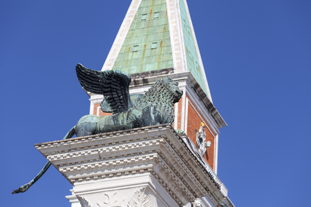 Column of San Marco and St Marks Campanile on Piazza San Marco , Venice, Italy. Lion of Saint Mark is ancient bronze winged lion sculpture, symbol of the city