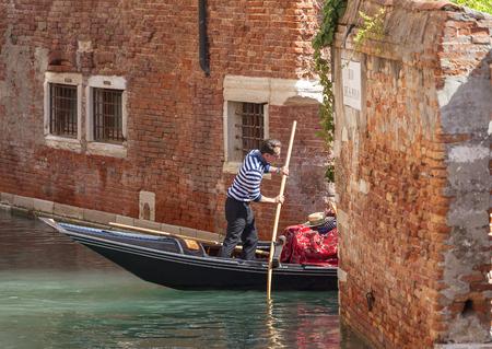 VENEZIA, ITALIA - 22 SETTEMBRE 2017: gondoliere veneziano che canta attraverso il canale stretto laterale. Gondola è barca tradizionale iconica, mezzo di trasporto molto popolare per i turisti