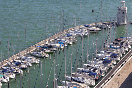 VENICE, ITALY - SEPTEMBER 21, 2017: Yacht harbor and lighthouse off the coast San Giorgio island. It is small island of the Venetian Lagoon, opposite St. Marks Square