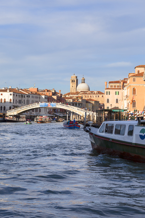VENICE, ITALY - SEPTEMBER 20, 2017: Grand Canal, Ponte degli Scalzi, vintage buildings, parked boats at the marina. Canal Grande is one of the major water-traffic corridors in the city, it is 3.8 km long Editorial