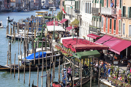 VENICE, ITALY-SEPTEMBER 22, 2017: View of the boulevard over the Grand Canal and harbor for gondolas.The Boulevard at Rialto Bridge is a place full of tourists, there are many restaurants and shops