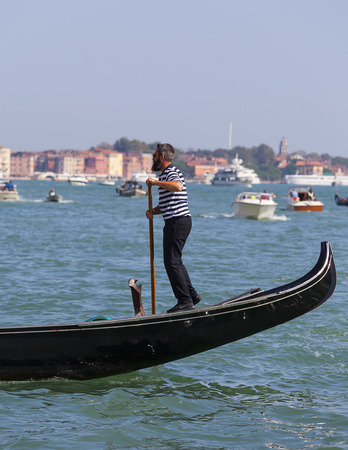 VENICE, ITALY-SEPTEMBER 22, 2017: Venetian gondolier rowing through the Grand Canal. Gondola is iconic traditional boat, very popular means of transport for tourists...