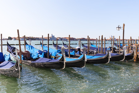 VENICE-ITALY, SEPTEMBER 21, 2017: Gondolas at the marina at the boulevard. Gondola is iconic traditional boat, very popular means of transport for tourists