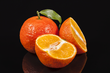 Fruits of mandarin orange ,whole and cut, on black background, reflection Stock Photo