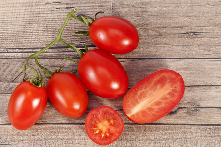 Vegetables of fresh tomatoes, whole and sectioned, on wooden plank, close up